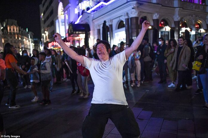 LONDON: People are seen dancing to a busker's music in Leicester Square in London on Saturday night ahead of the new rules