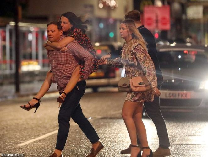 LEEDS: A woman is given a piggie-back across in a road in Leeds, Yorkshire, as people enjoy a final hurrah on the last weekend before rule changes
