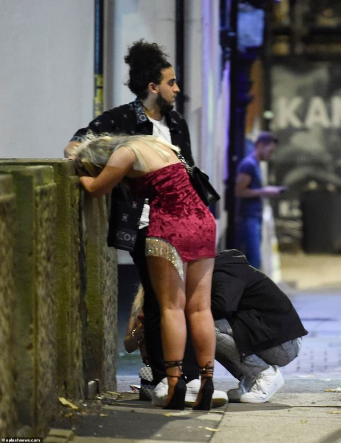 MANCHESTER: One reveller rests her head on a concrete wall in Manchester as other revellers stand around in the streets of Manchester
