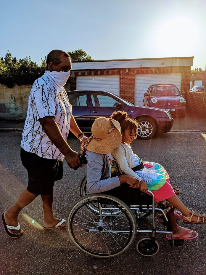 Grandma + Grandad = Love by Diane Bartholomew Magalhaes. A family is seen moving down a road together