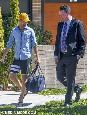 All smiles: Clad in a denim button-up shirt and black boardshorts, the anti-vaxxer grinned as he enjoyed a breezy discussion with his agent