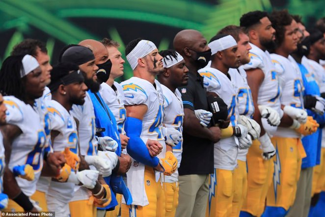 The Los Angeles Chargers stand arm-in-arm before their game against the Cincinnati Bengals in Cincinnati