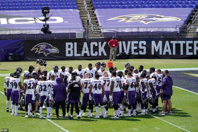 Baltimore Ravens players gather on the field before and NFL football game against the Cleveland Browns on Sunday in Baltimore