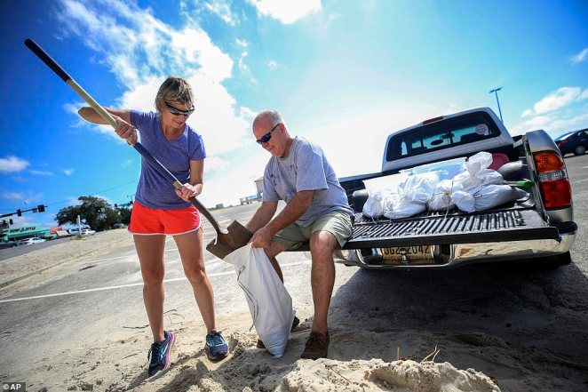 Mississippi Coast residents fill sandbags. Kim Miller and Monty Graham opened their truck bed and began loading up sandbags along U.S. 90 in preparation for Tropical Storm Sally, Sunday