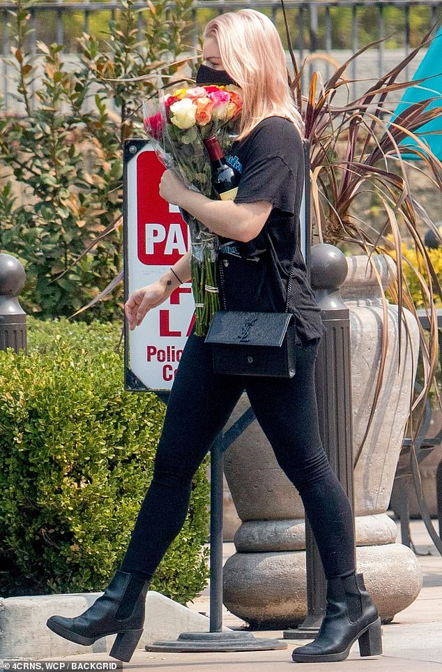 Back in black: The 22-year-old donned a retro black printed t-shirt from a pool hall in Irvine, California, with matching skintight leggings