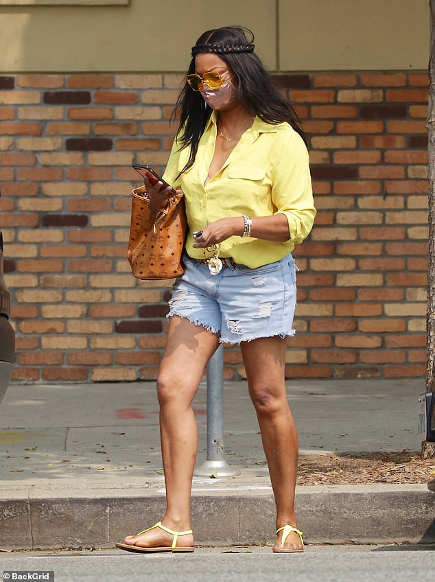 Casual style: The actress and reality star, 57, paired her outfit with yellow flip-flops and yellow-tinted glasses and carried a large leather designer tote over one shoulder as she walked