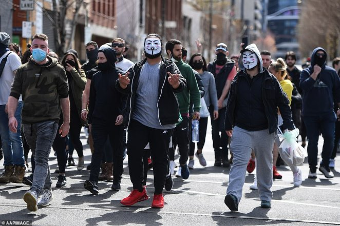 Protesters in Guy Fawkes masks march during an anti-lockdown demonstration in Melbourne's central business district on Sunday