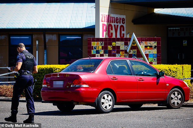 A red car pictured at the scene is reportedly making up part of the police investigation