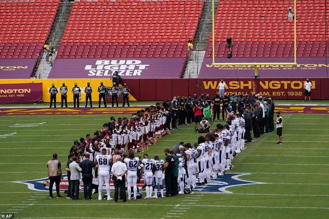 Members of the Washington Football Team and Philadelphia Eagles form an oval on the field before the start of their game