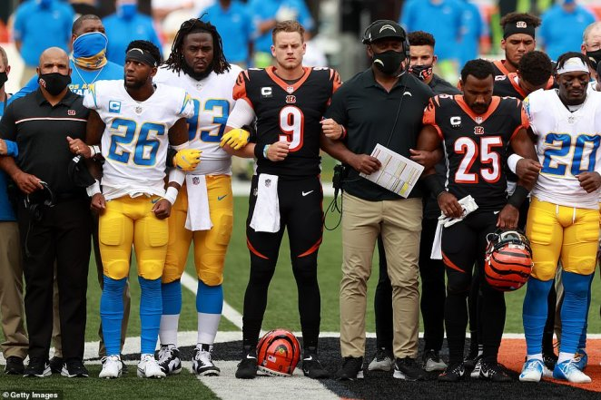 Quarterback Joe Burrow #9 of the Cincinnati Bengals, teammates and the Los Angeles Chargers stand in unity during the U.S. National Anthem at Paul Brown Stadium