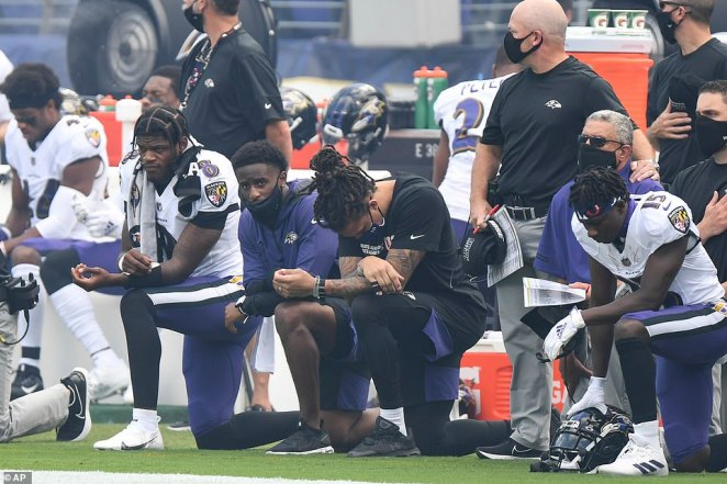 Baltimore Ravens quarterback Lamar Jackson (8) and teammates kneel during the National Anthem before an NFL football game against the Cleveland Browns, Sunday