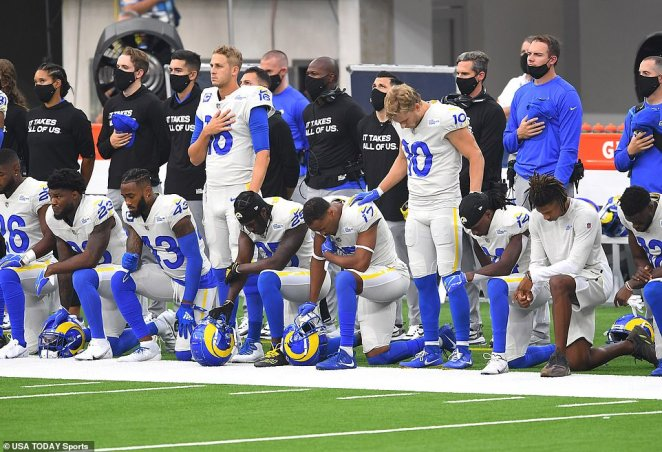 Los Angeles Rams players on the sidelines during the National Anthem before the game against the Dallas Cowboys at SoFi