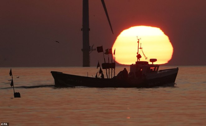 A fishing boat sails in front of the rising sun near Blyth pier in Northumberland at the start of the week of warm weather