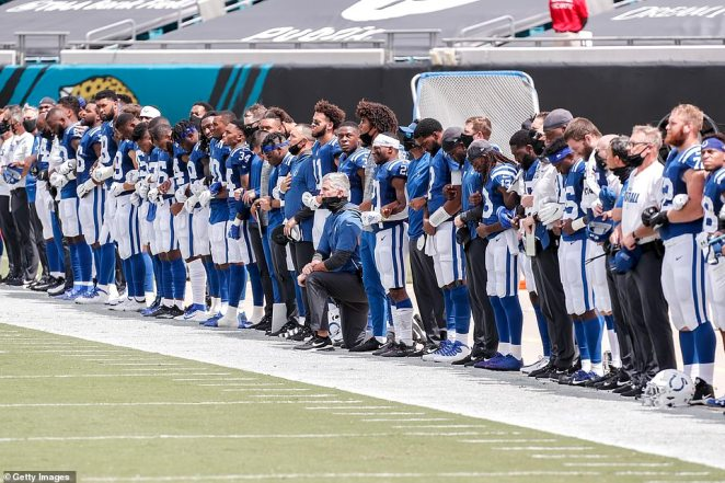 Head Coach Frank Reich of the Indianapolis Colts takes a knee during the National Anthem with his team before the start of the game against the Jacksonville Jaguars at TIAA Bank Field on Sunday