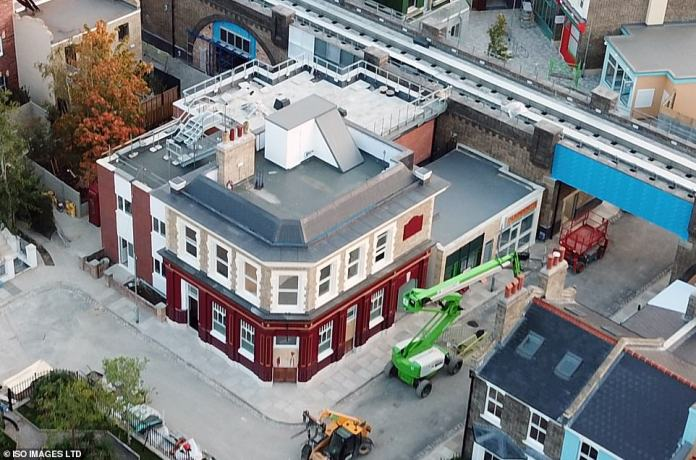 There it is: The completed Queen Victoria pub is visible in all its glory as set designers add the finishing touches to the square