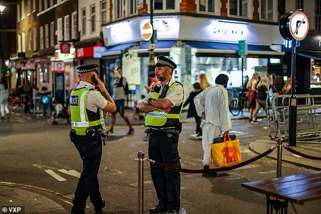 Crackdown: Police in Soho on Sunday night as people enjoyed their last night out before the 'rule of six' on social gatherings comes into effect today