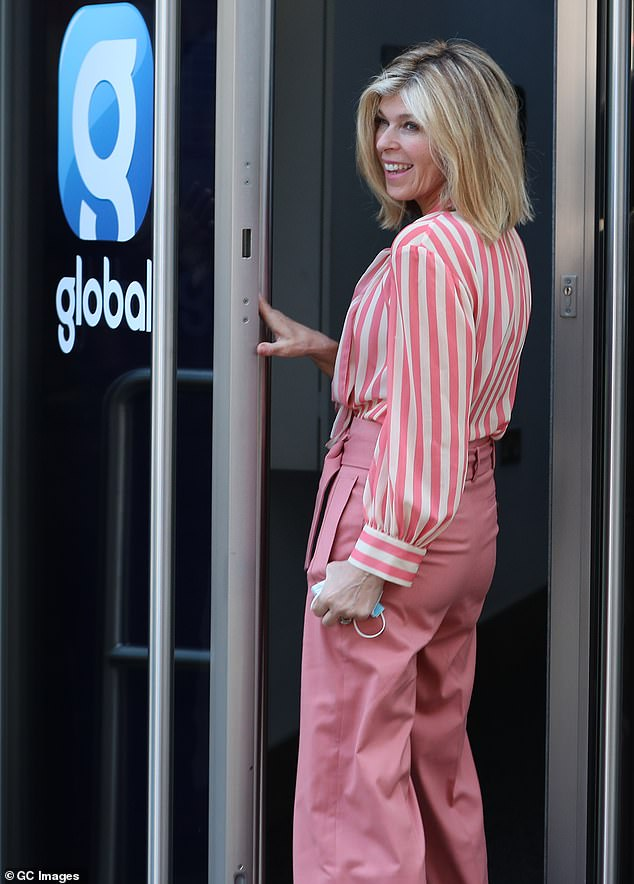 All smiles: Kate turned back to beam at the cameras as she pulled open the door to the studios in London