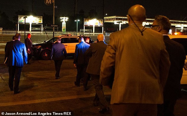 Detectives are pictured arriving at the scene of Saturday's shooting in Compton