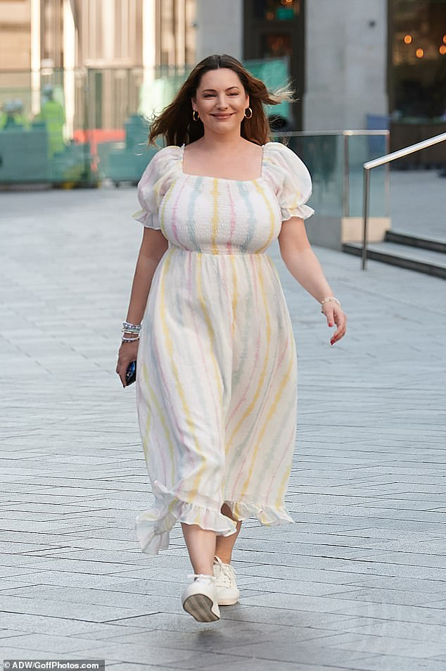 Summery:Featuring a ruched bust and milkmaid sleeves, the colourful midi clung to her ample chest and skimmed out to a calf length hem
