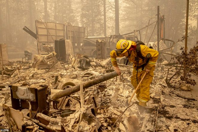 Berry Creek volunteer firefighter Zack Gable sifts through charred rubble from the Bear Fire