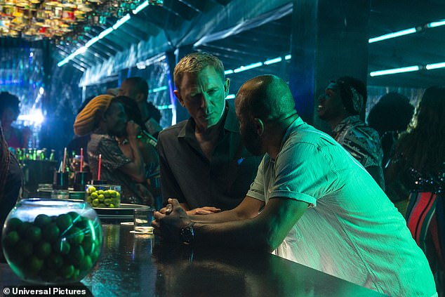 Scene: In the new images, Bond is in a crowded bar dressed in a black shirt as he speaks in hushed tones to a man