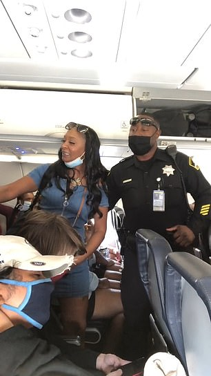 After a few minutes, an officer arrives and asks the woman to leave the plane