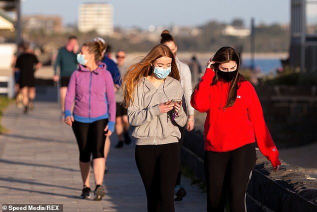 Masked walkers on South Melbourne Beach on Monday as the world's heaviest coronavirus restrictions were eased to allow residents two hours exercise time