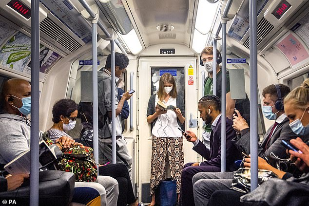 He points out that the Covid-19 death rate is extremely low —comparable, in fact, to the 12 people under the age of 35 who die each week from undetected heart problems. People are pictured on the Jubilee Line on the London Underground