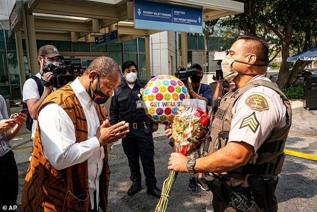 Nazi Ali of Project Islamic Hope, presents Sergeant.  Larry Villarreal of the Los Angeles County Sheriff Department, flowers to a depot that recovers at St. Francis Medical Center on Monday