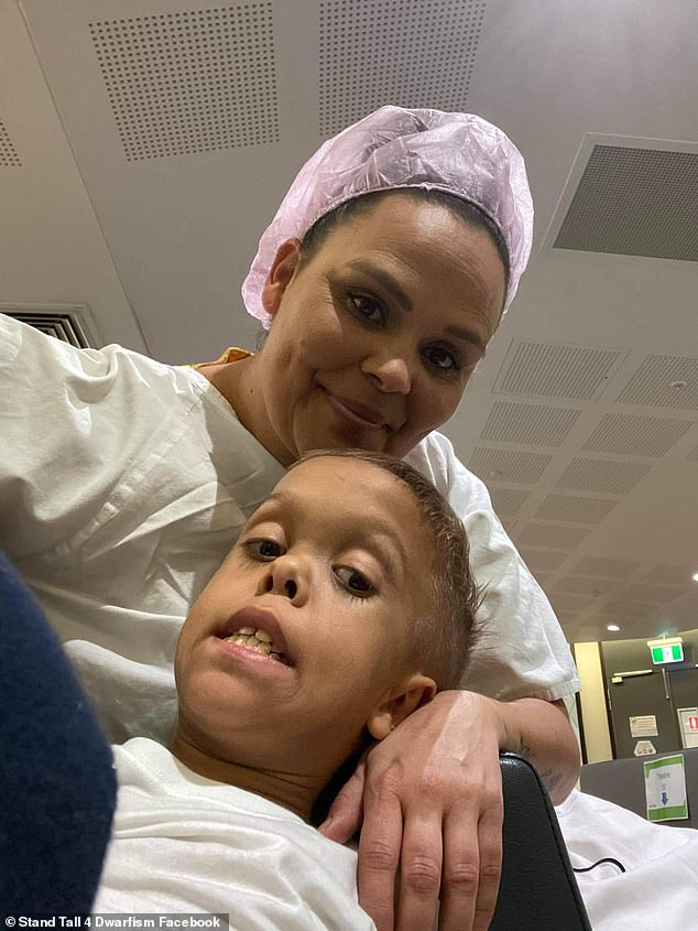 The nine-year-old underwent surgery at Queensland Children's Hospital on Monday to remove eight of his teeth removed due to overcrowding (pictured with his mother Yarraka)