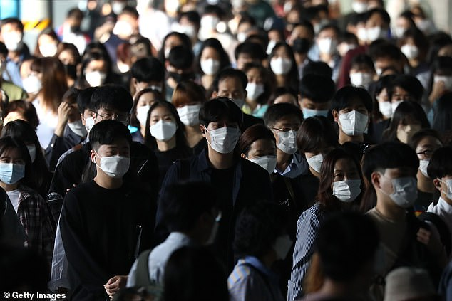 Commuters get off a train during rush hour in Seoul this morning with most of the country's new cases coming in or near the capital city
