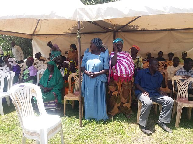 Well-wishers and mourners gather in a tent during the funeral service for Mercy Baguma