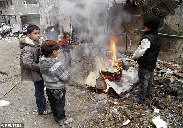 Children warm themselves around a fire in Homs, Syria, in 2014