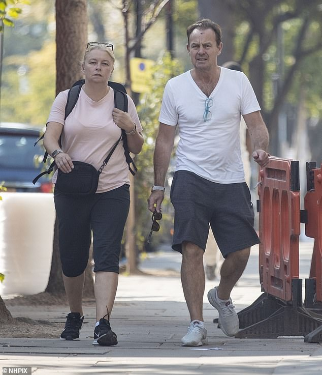 Looks like a real headbanger: Jason Donovan, 52, did little to dispel rumours he's signed up for Dancing On Ice as he was seen with an injury during a morning stroll with wife Angela