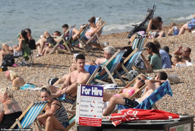 Sun-lovers enjoying the warm weather on a beach in Brighton this morning, as Britain enjoys an Indian summer up to next week