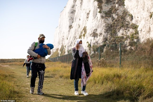 Wearing a face-mask, puffer jacket and Adidas tracksuit, the father was this morning photographed walking with his wife and two children along the coastal path at Kingsdown Beach in Deal