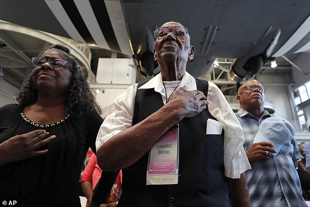 Lawrence Brooks holds his hand to his heart during the singing of the National Anthem on his 110th birthday at the National World War II Museum in New Orleans last year