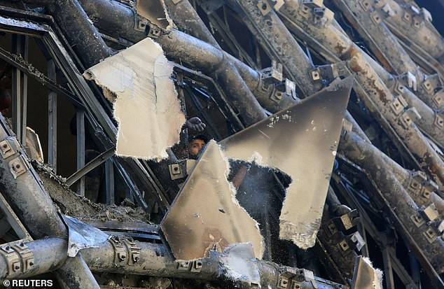 A man inspects the damage as pieces of debris hang from the side of the landmark building
