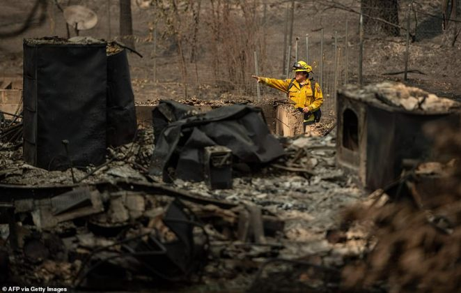 Firefighters search through a burned residence after the passage of the Bear fire, part of the larger North Lightning Complex fire, in the Berry Creek area of unincorporated Butte county, California on Monday