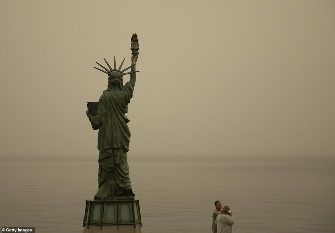 A couple walks by a small replica of the Statue of Liberty as smoke from wildfires fills the air at Alki Beach Park in Seattle on September 12
