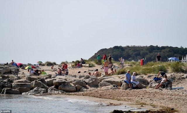 Beach goers enjoy the warm temperatures at the exclusive Mudeford Sandbank beach in Dorset