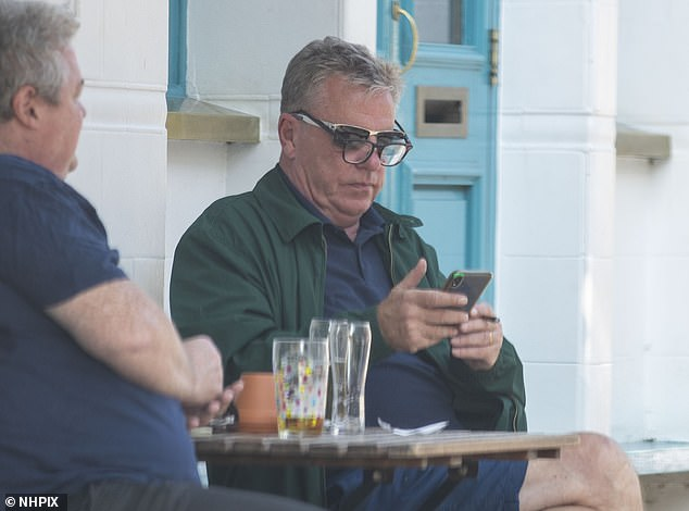 What a sight: Madness star Suggs was seen wearing spectacles over his sunglasses as he scrolled through his phone while drinking with a friend in London on Tuesday