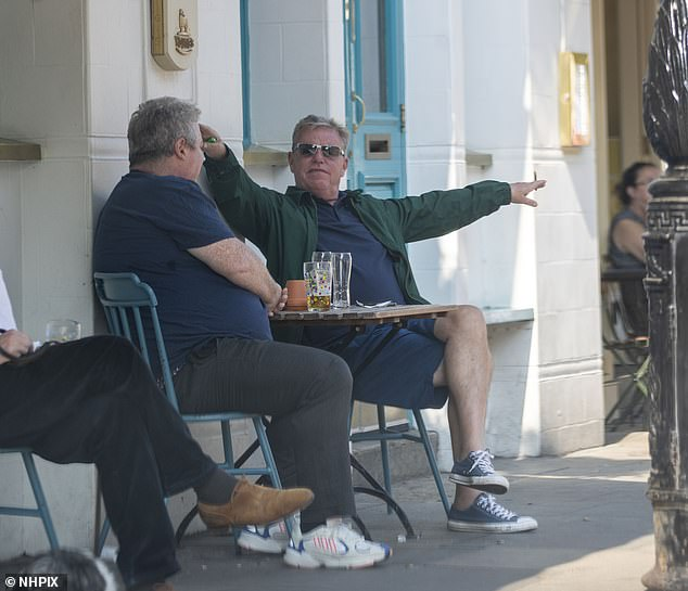 Fun: The star was seen getting animated as the pair indulged in their al fresco beers in the sun