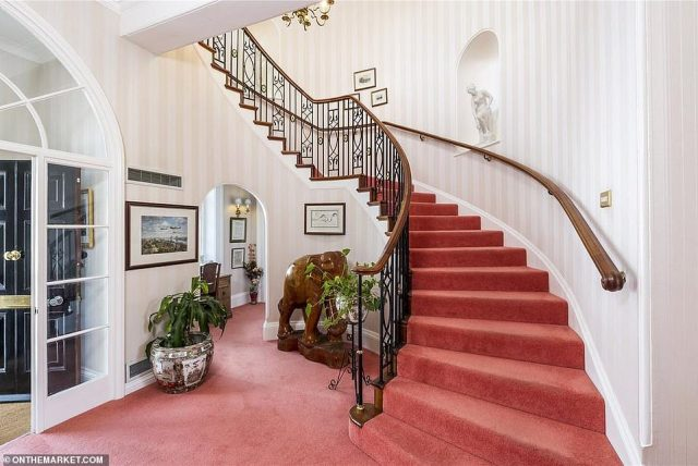 The home boasts a reception hall with a sweeping staircase (pictured), a drawing room, dining room, sitting room, family room, study, kitchen and utility rooms