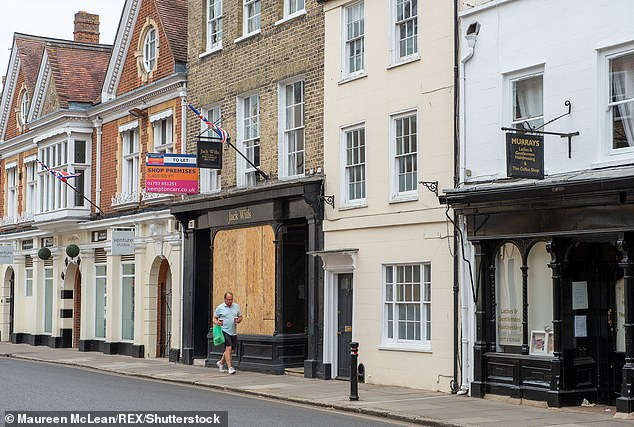 A man walks past a boarded up former Jack Wills shop in Eton High Street,Berkshire