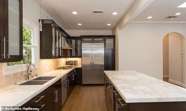 Clean: An open-concept kitchen includes dark marble cabinets with white marble countertops and stainless steel appliances