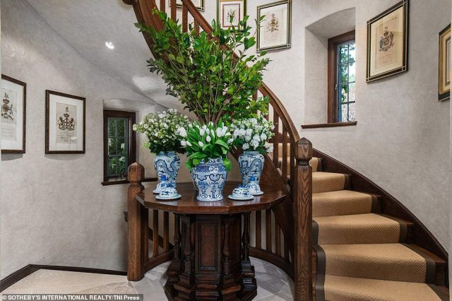 A spiral staircase in the Greenwich is accented by floral vases with flowers