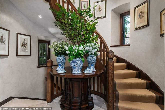 A staircase in the home is accented by floral vases with flowers