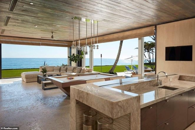 The home seamlessly blends indoor and outdoor living, as evidenced by this games room as bar pictured above