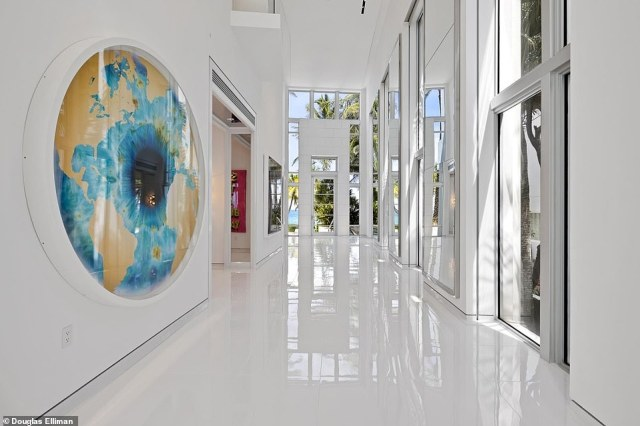Florida estate: The white entrance gallery includes a chrome Mickey Mouse sculpture and a curved staircase but once inside, it's vibrant decor that dominates